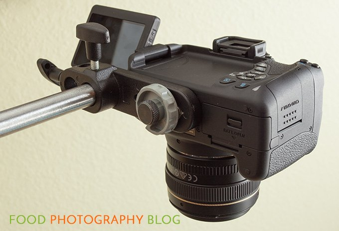 Close up image of a camera mounted onto the Manfrotto camera bracket that is mounted onto the end of a c-stand arm