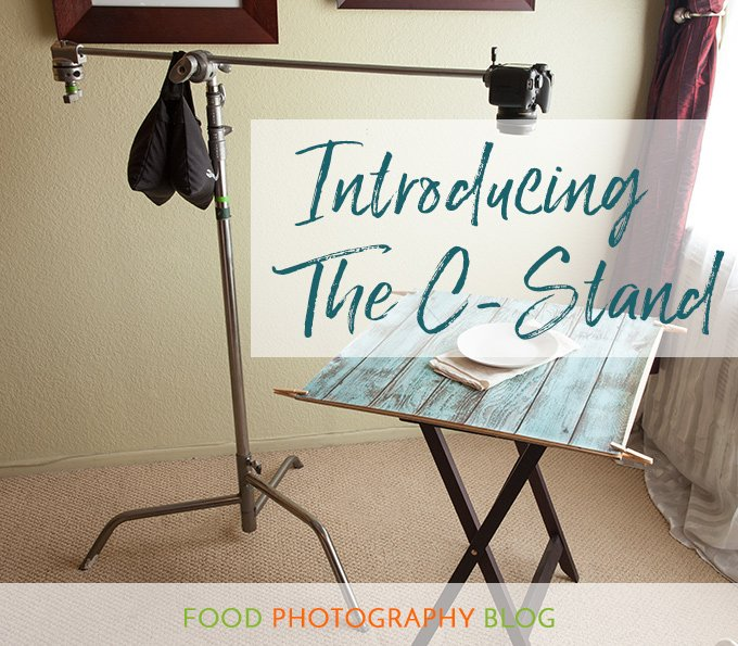 "Blog post title image showing a camera mounted to the end of a c-stand arm with the text, ""Introducing the C Stand"" on top of the image"