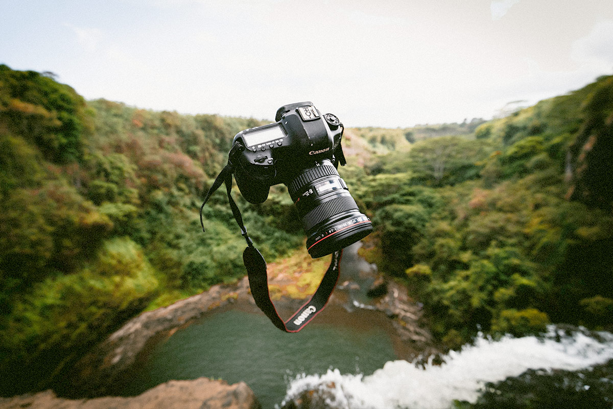 Image of camera falling with a landscape in background