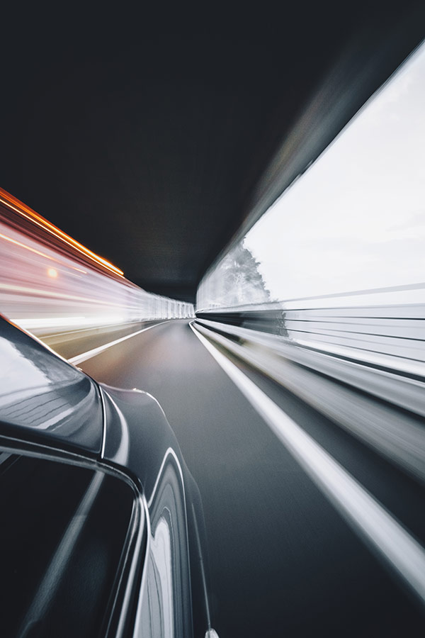 Image of a car on a road driving with motion blur