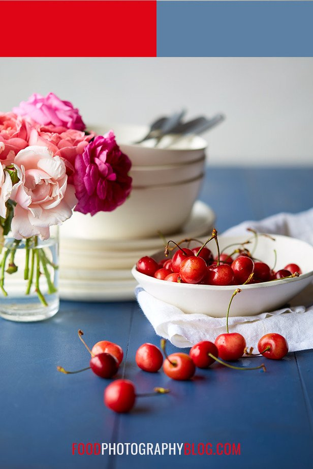 Image of cherries in a white bowl on a blue table
