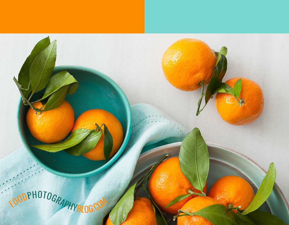 Image of tangerines in a blue bowl on marble surface