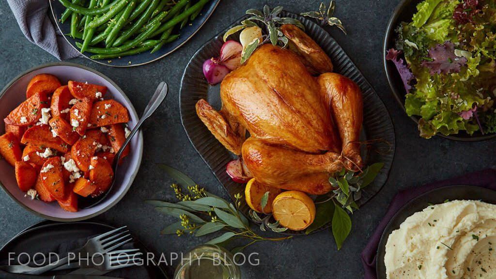 Image of a cooked chicken with side dishes on a dark background shot from ovehread